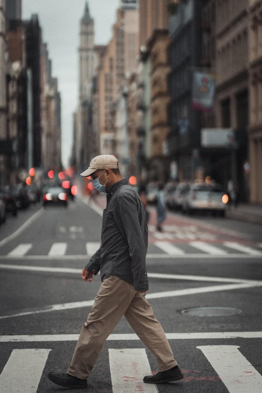 man in black and white pinstripe dress shirt and brown pants walking on pedestrian lane during