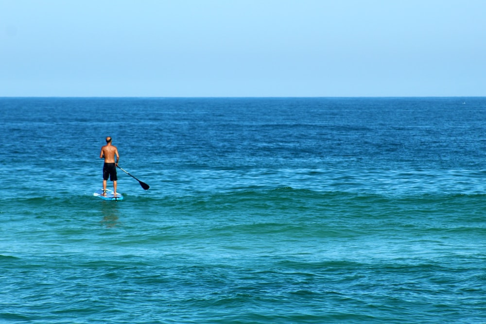 man in black wetsuit riding on white surfboard on sea during daytime