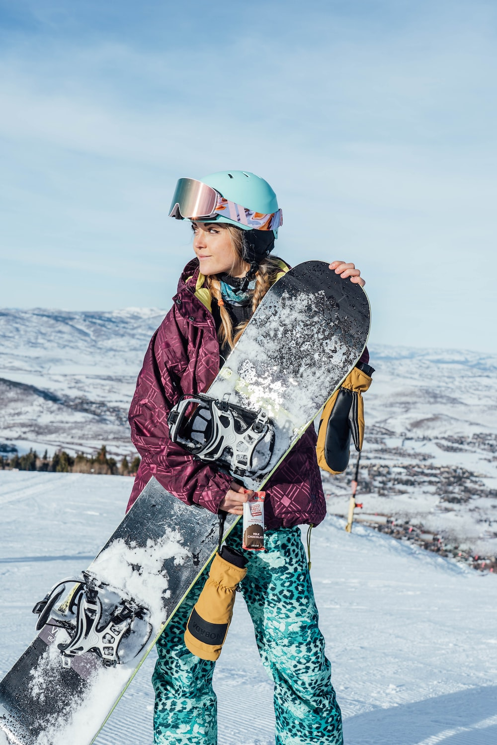 woman in black and white floral jacket and blue pants wearing black and white snow goggles