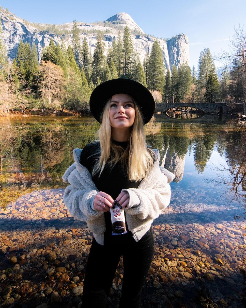 woman in gray jacket standing near lake during daytime