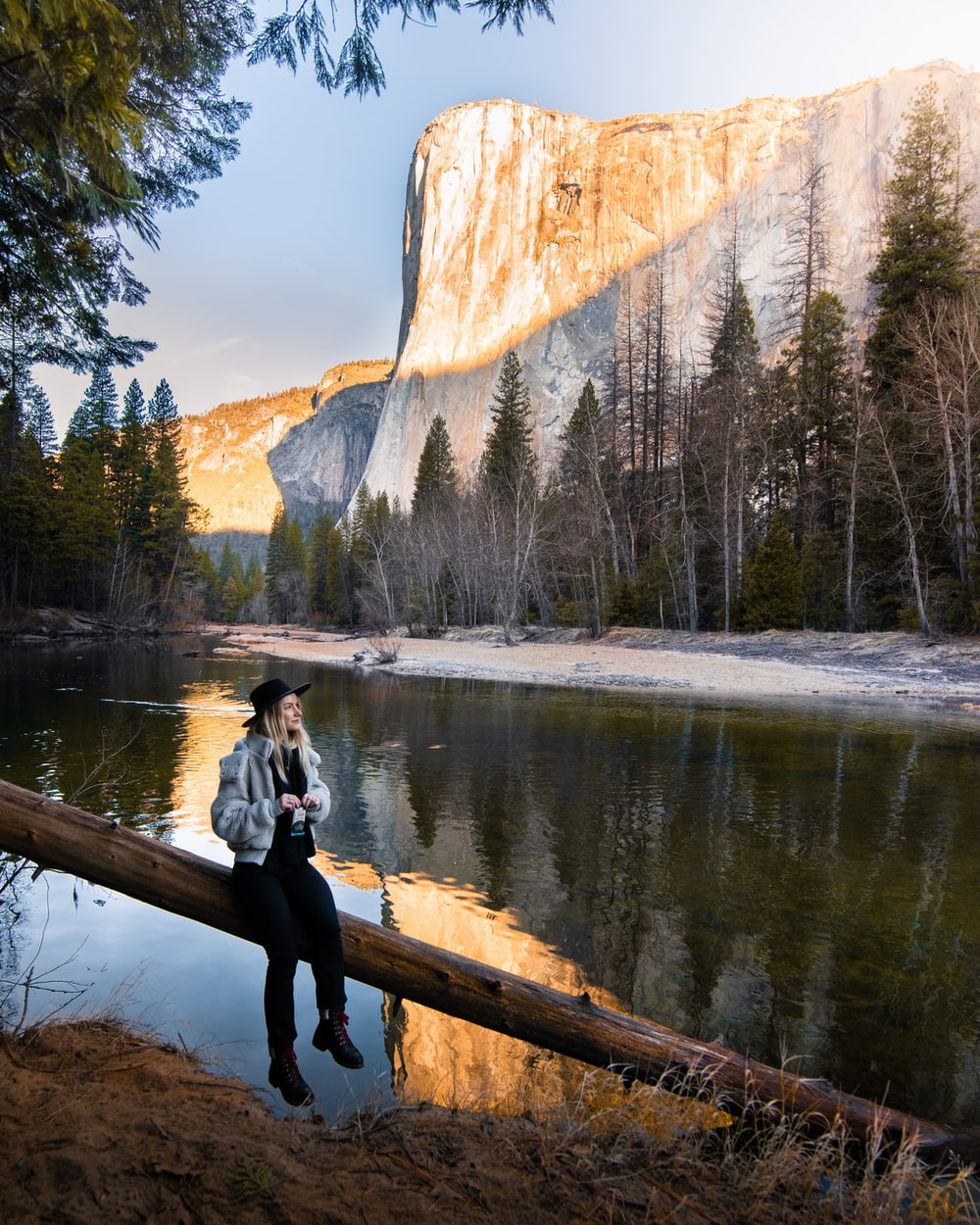 woman in gray long sleeve shirt and black pants sitting on brown wooden log near lake