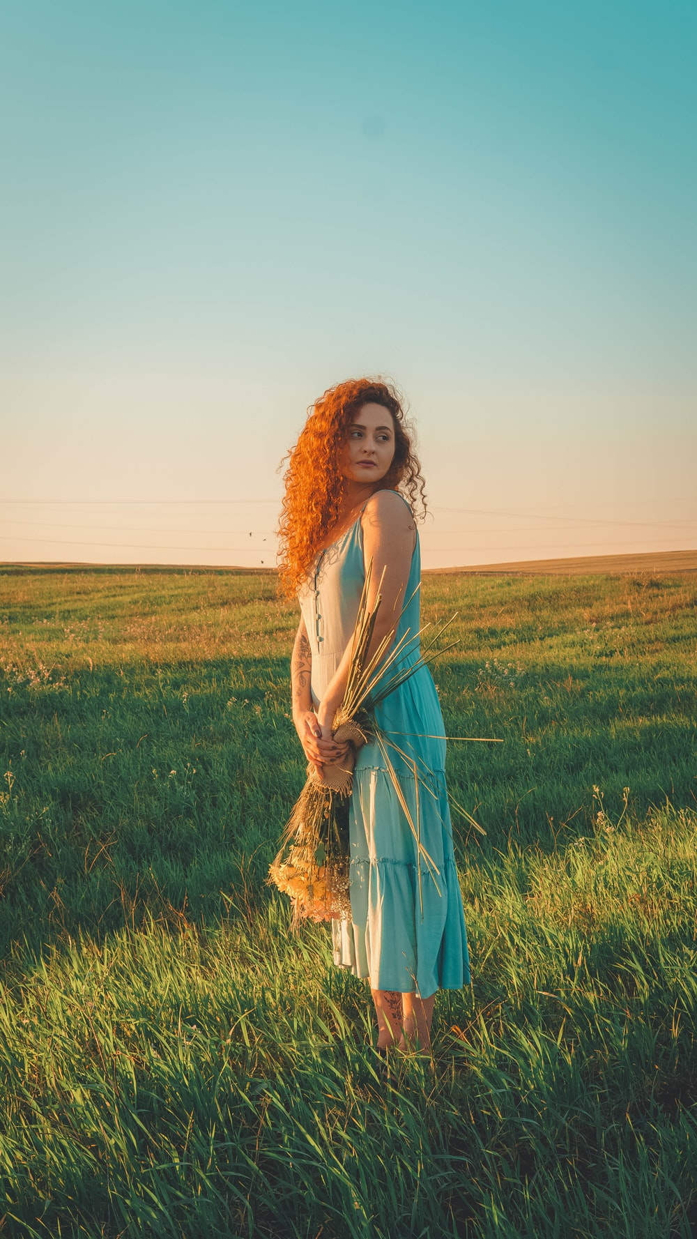 woman in blue sleeveless dress standing on green grass field during daytime