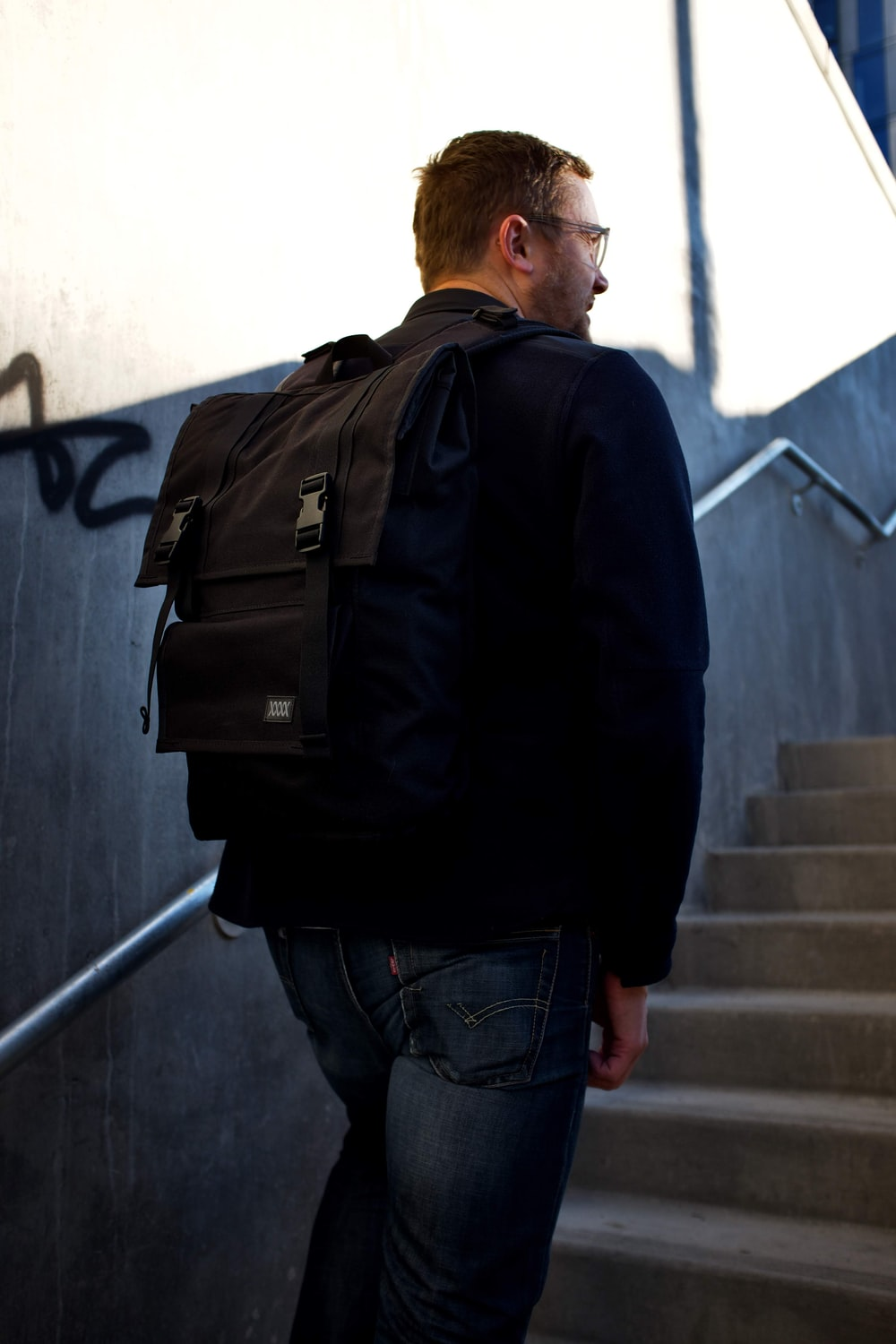 man in black jacket and blue denim jeans with black backpack standing on stairs