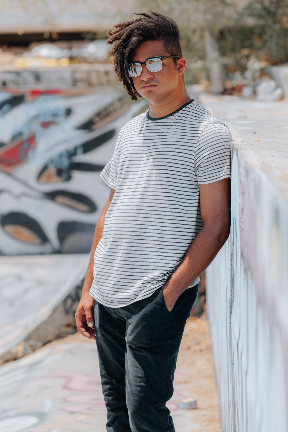 man in white and black striped crew neck t-shirt and black denim jeans standing on on near on near