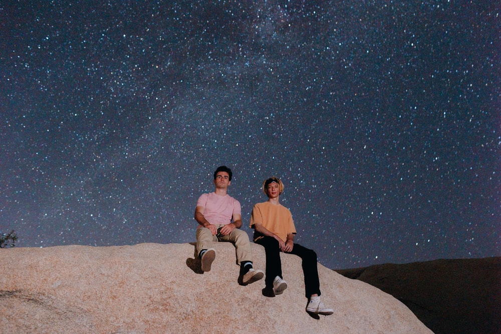 man and woman sitting on rock during night time