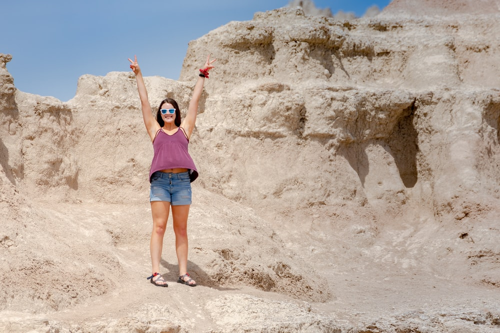 woman in blue tank top and blue denim shorts standing on brown rock formation during daytime
