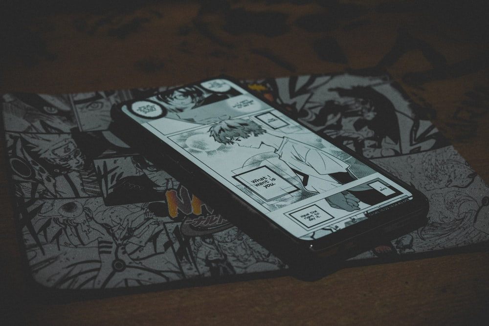 black smartphone on black and white floral textile