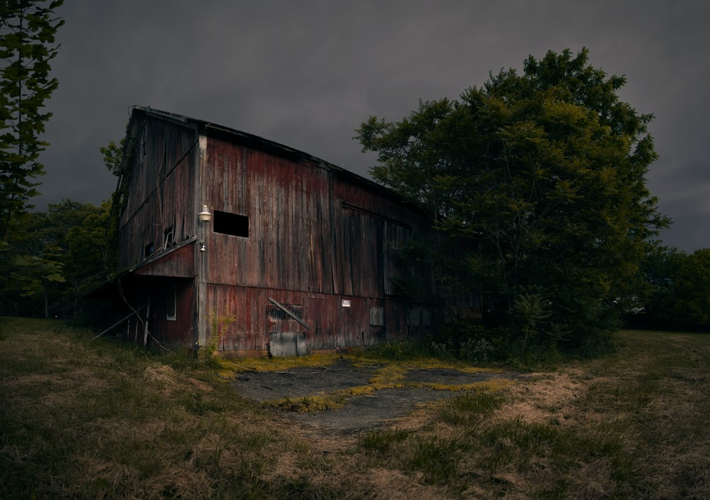 brown wooden barn under gray cloudy sky