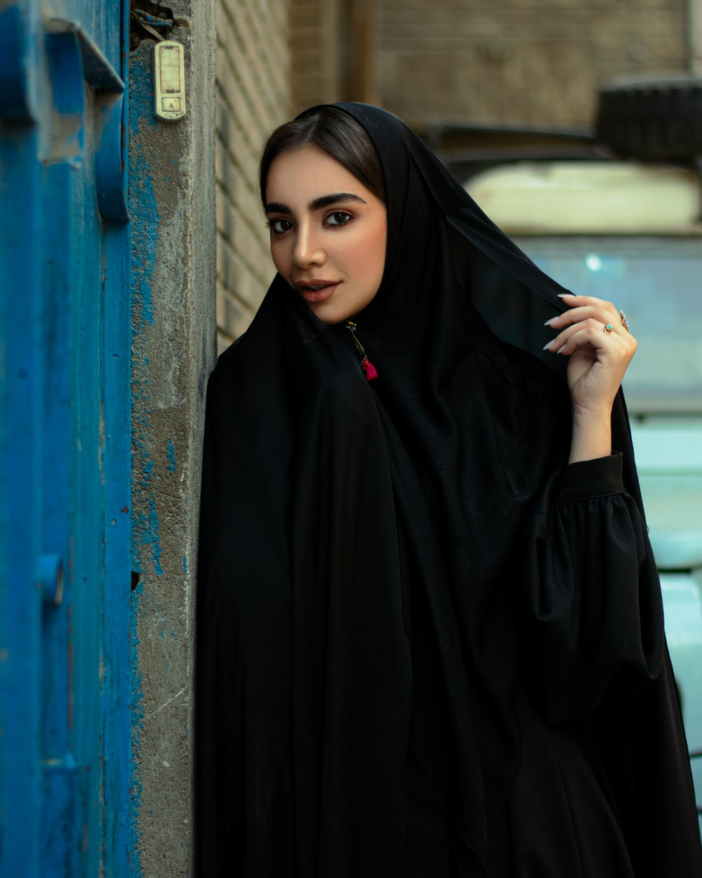 woman in black hijab standing beside blue wall