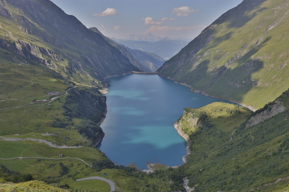 aerial view of lake in the middle of green mountains during daytime