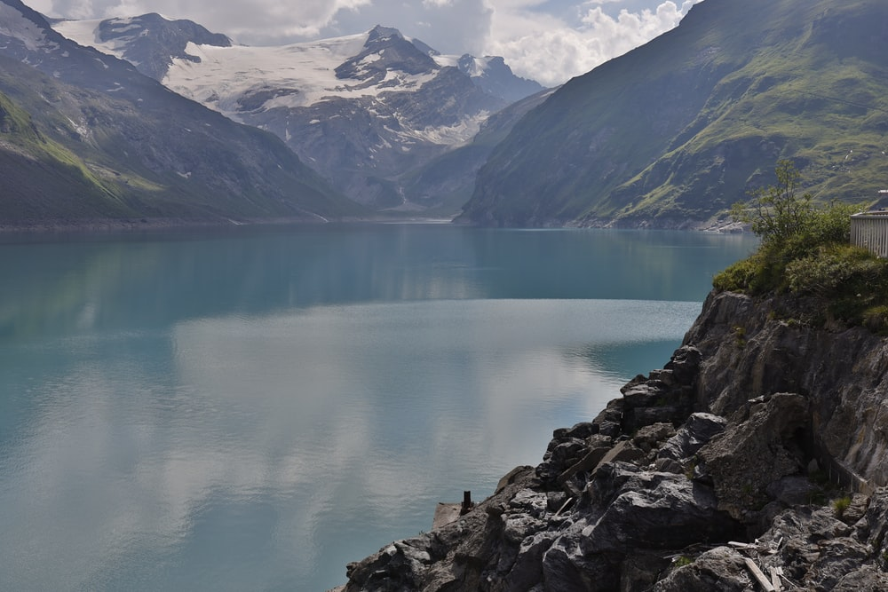 lake near mountain range under blue sky during daytime