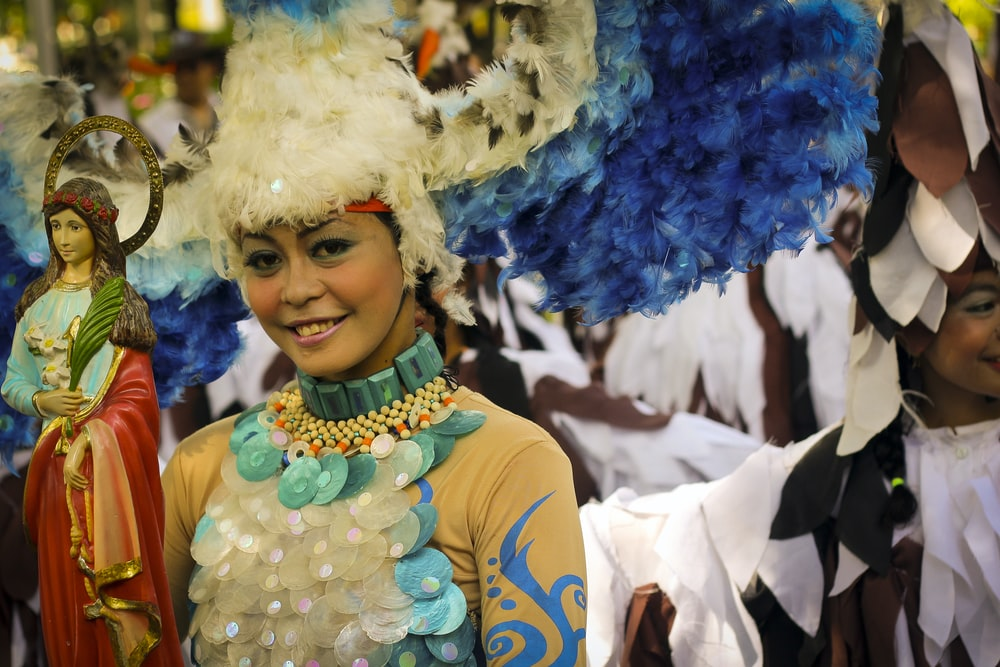 woman in blue and yellow dress with blue and white feather headdress