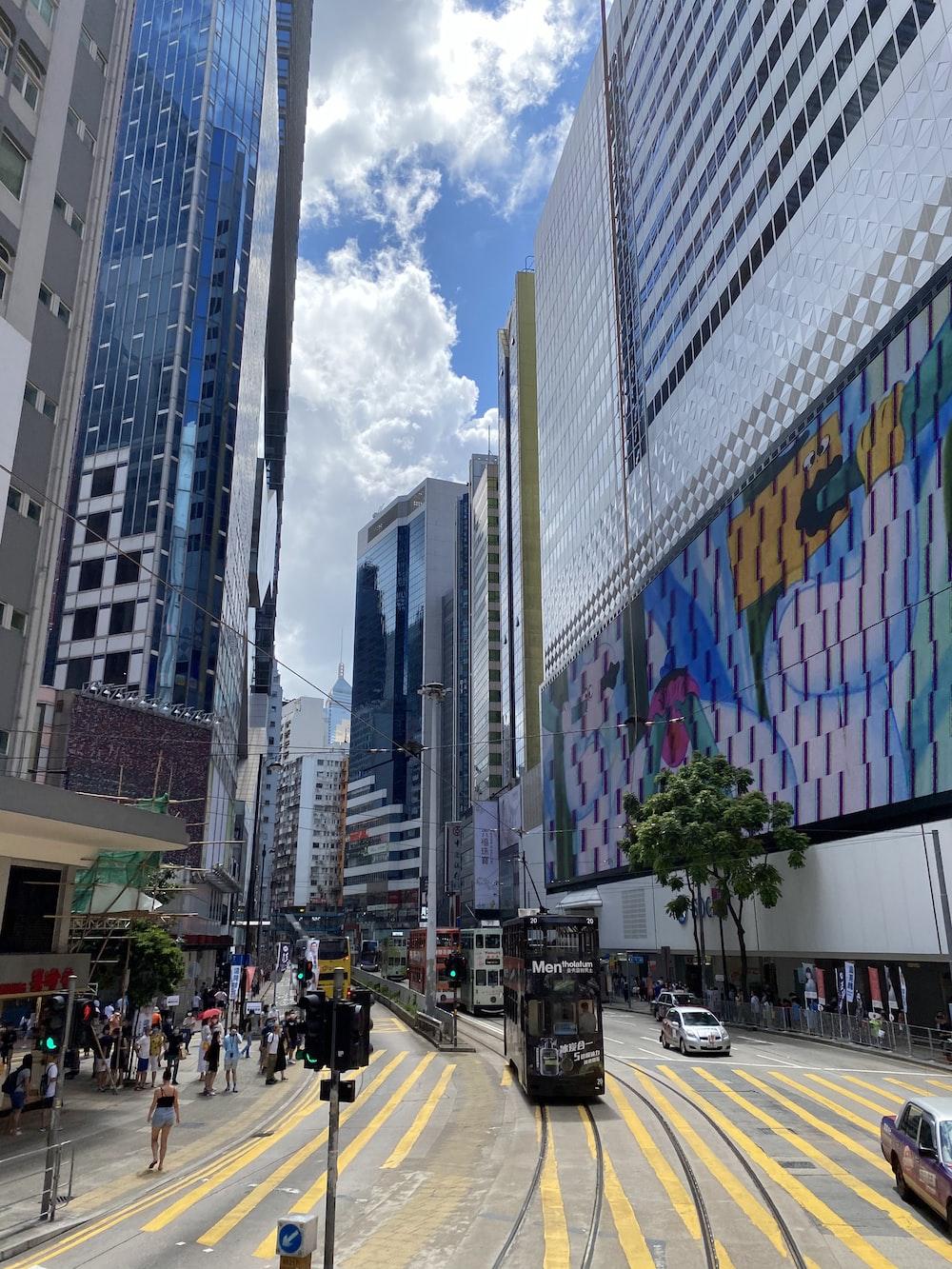 people walking on pedestrian lane near high rise buildings during daytime