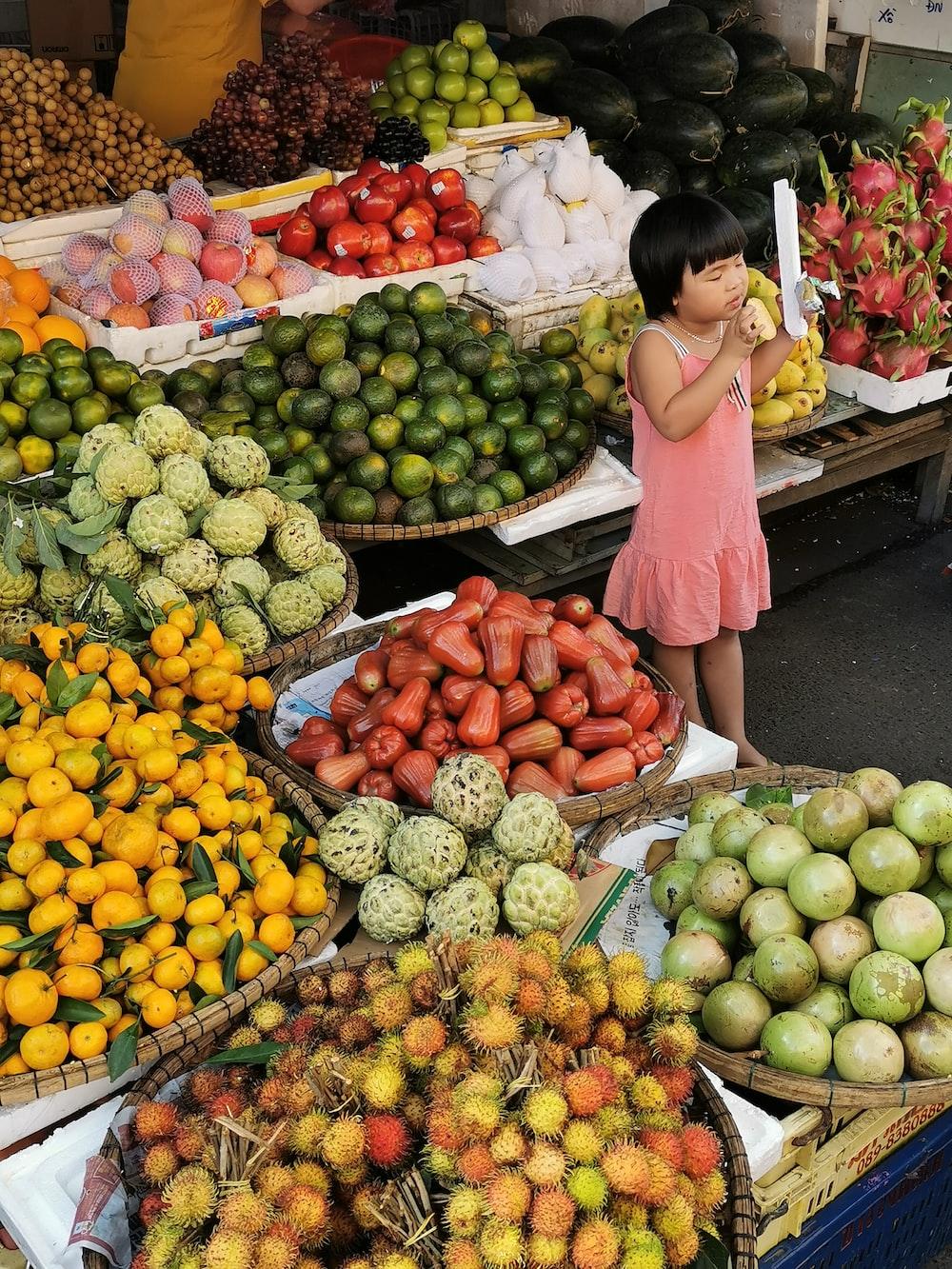 woman in pink long sleeve shirt standing beside fruits