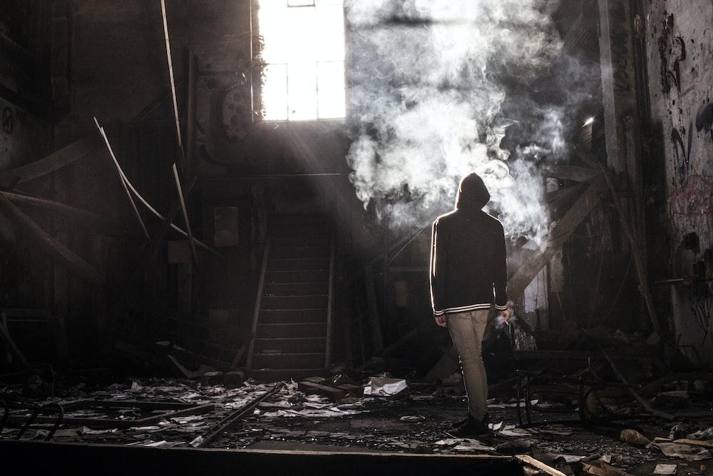 man in black shirt standing near brown wooden wall