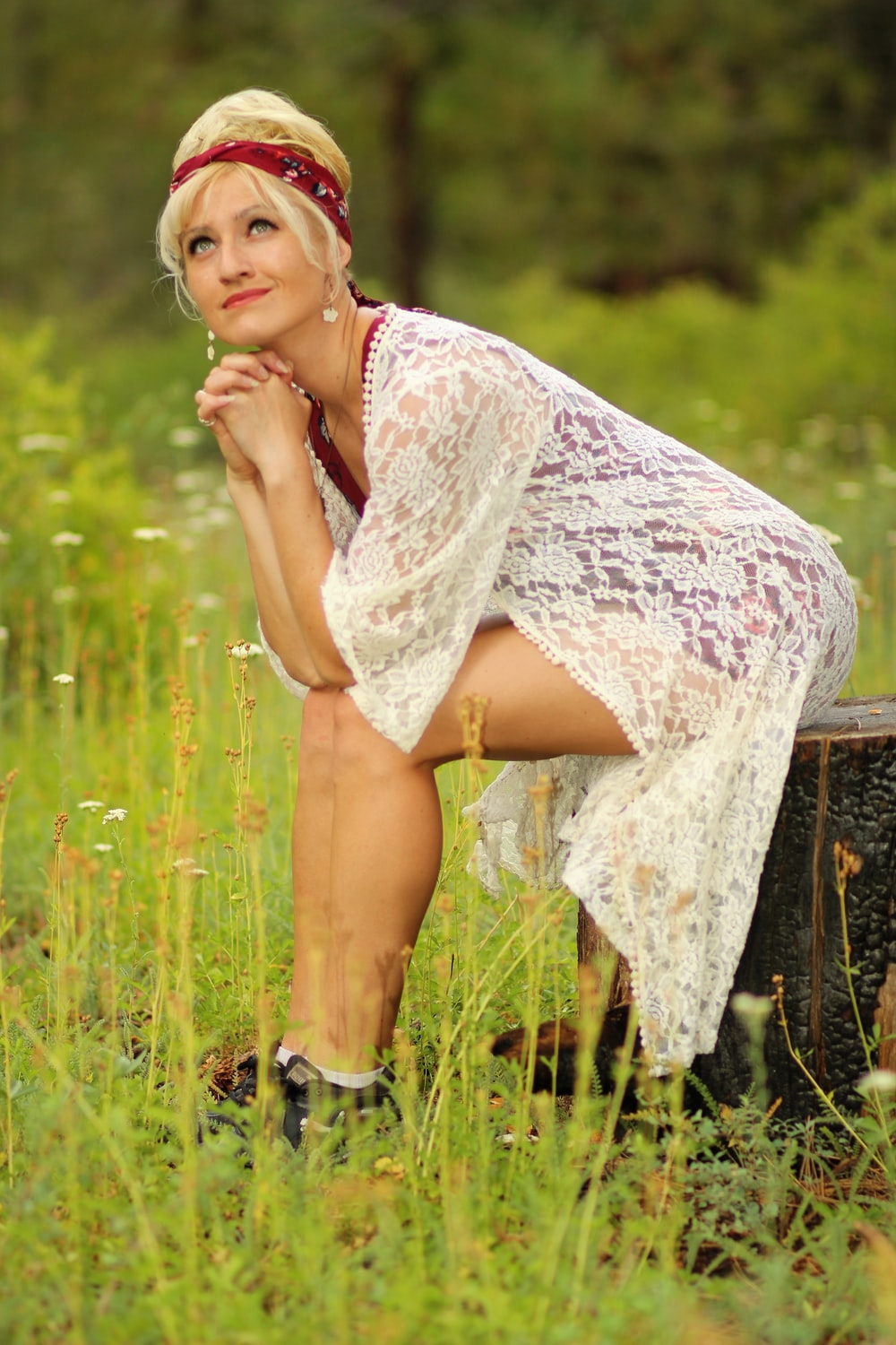 woman in white lace dress standing on green grass field during daytime