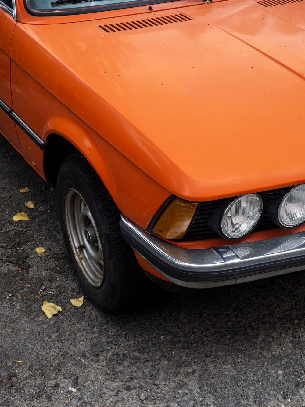 orange car on gray concrete pavement