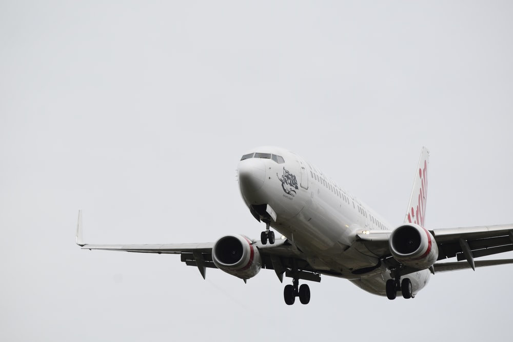 white and red airplane under white sky during daytime