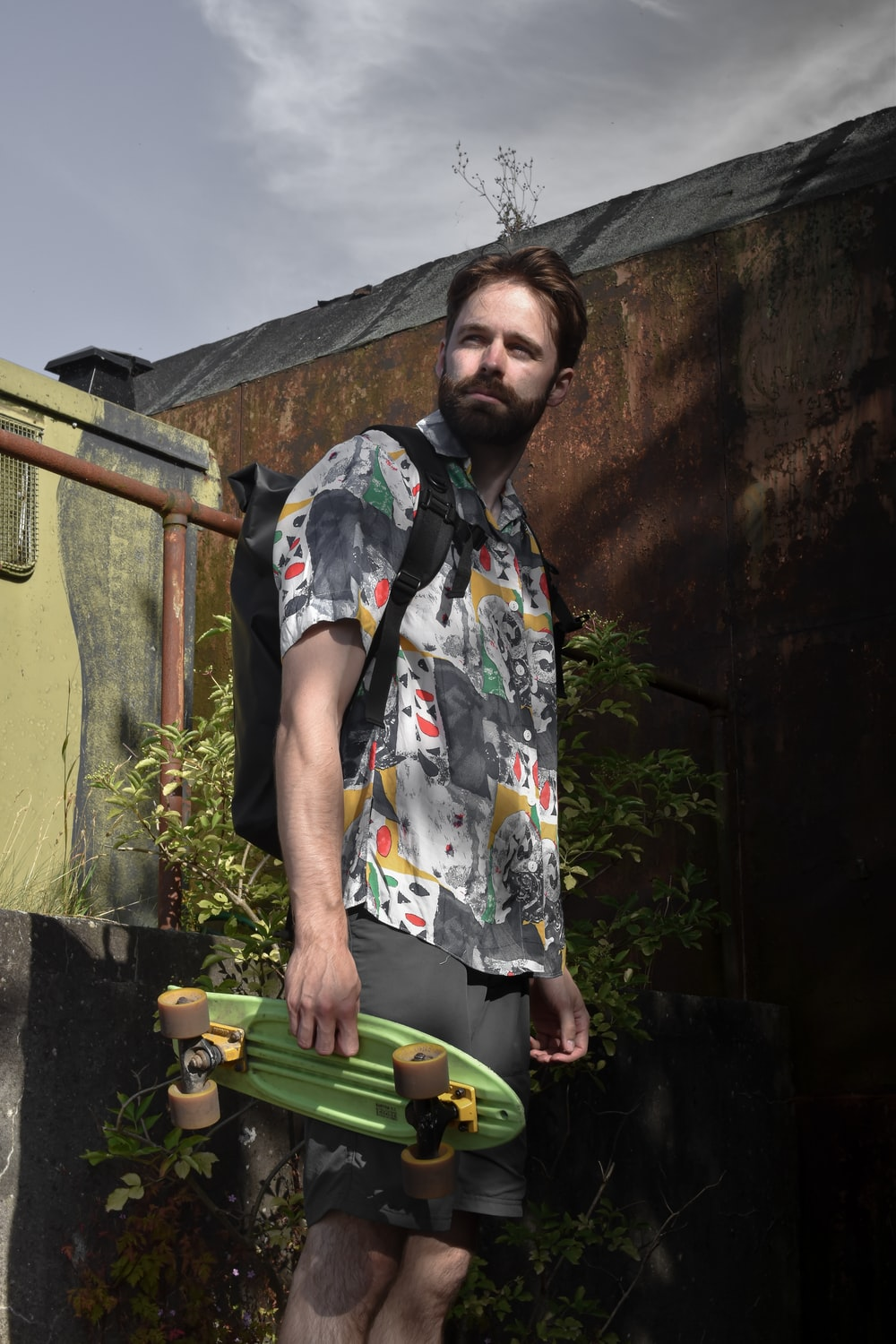 man in white blue and yellow floral button up t-shirt standing near brown concrete wall