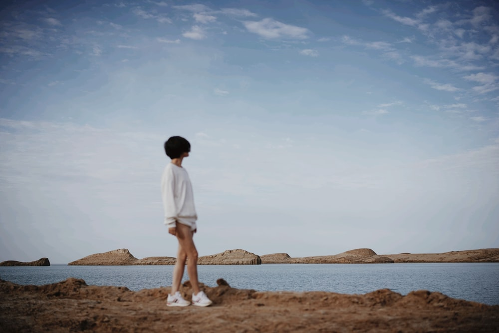 man in white t-shirt standing on brown sand during daytime