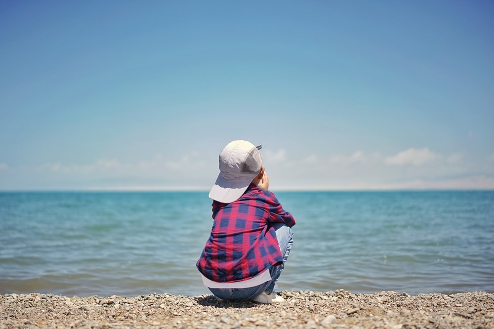woman in white knit cap sitting on brown sand near body of water during daytime