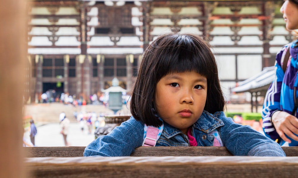 girl in blue denim jacket sitting on brown wooden bench during daytime