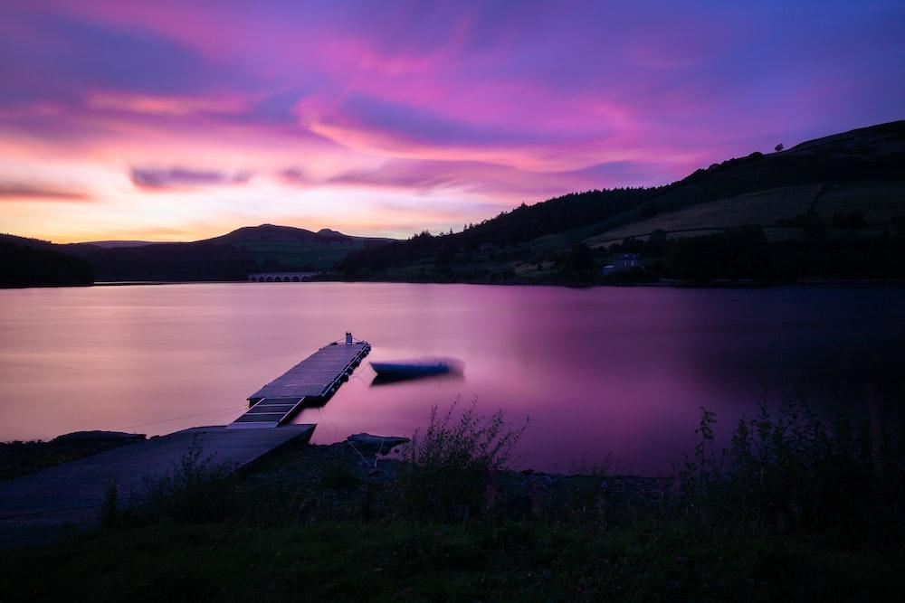 white wooden dock on lake during sunset