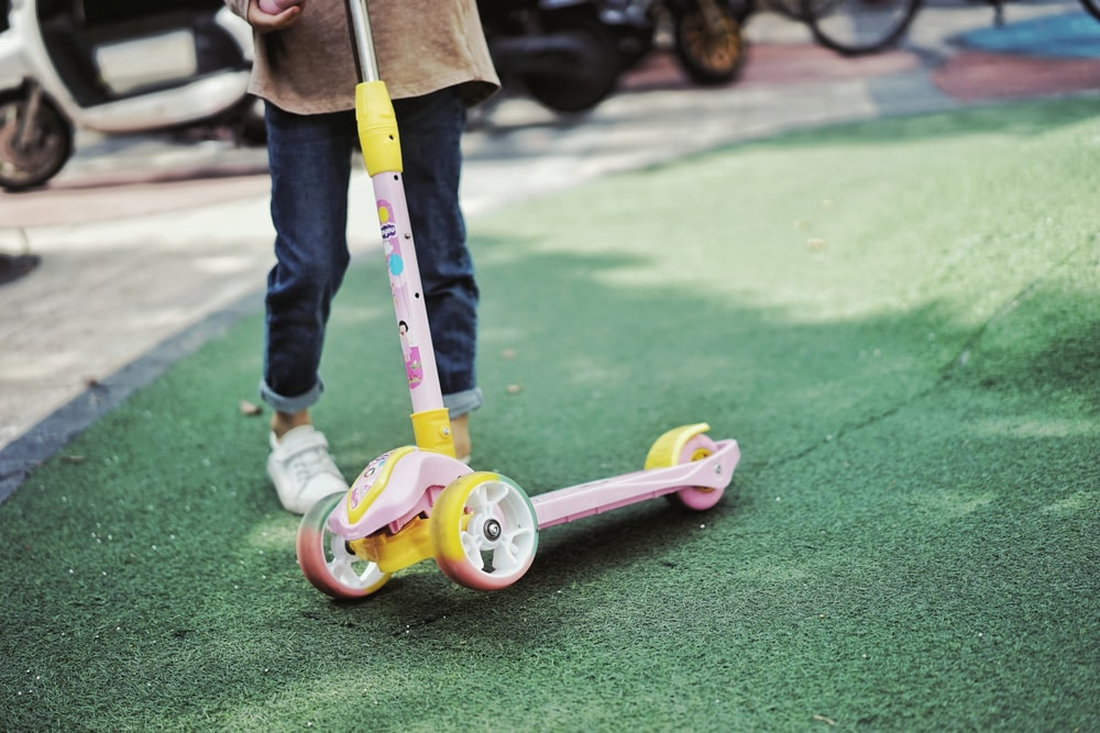 pink and white kick scooter on green grass field during daytime