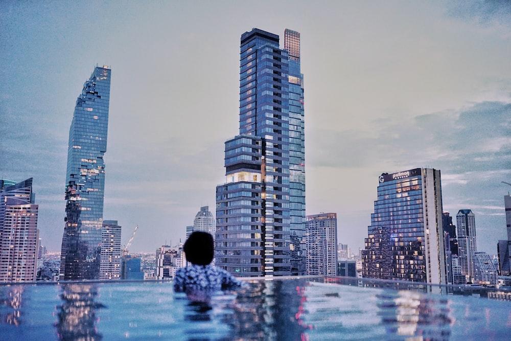 man in black hoodie standing in front of city buildings during daytime