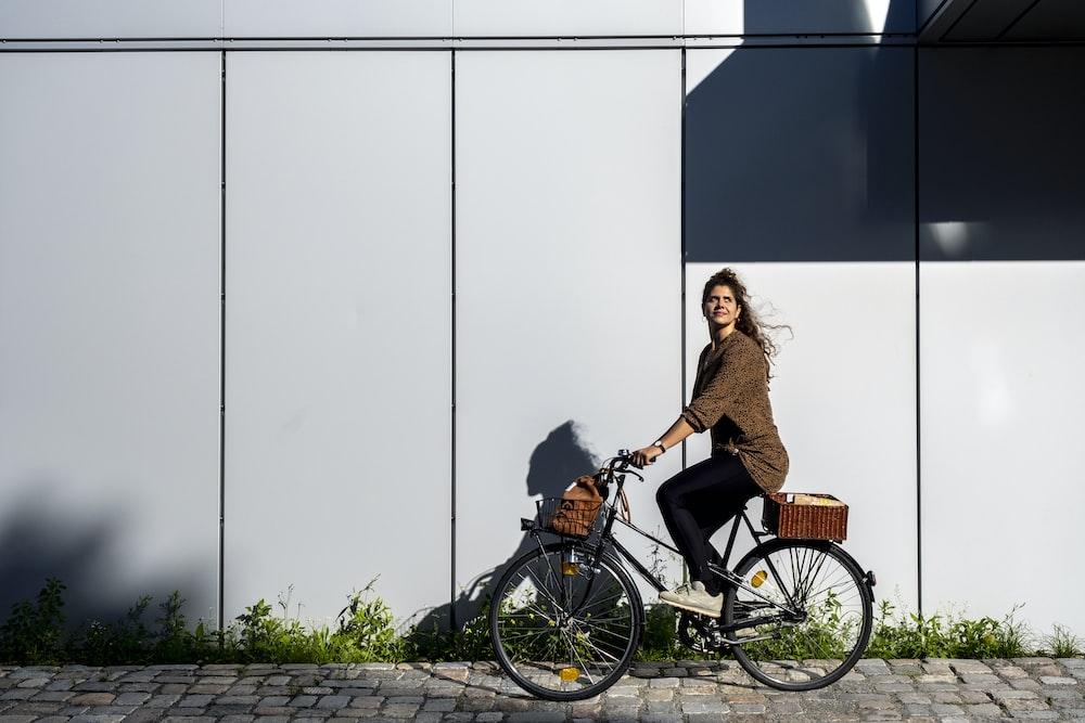 woman in brown dress riding on black city bike