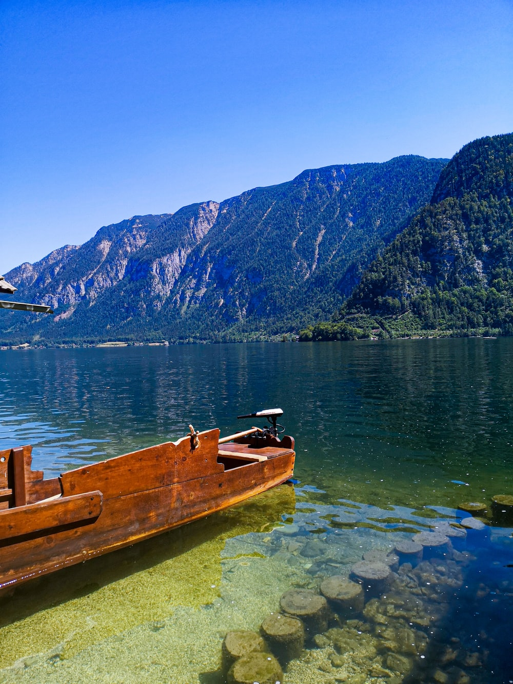 brown wooden boat on water near mountain during daytime