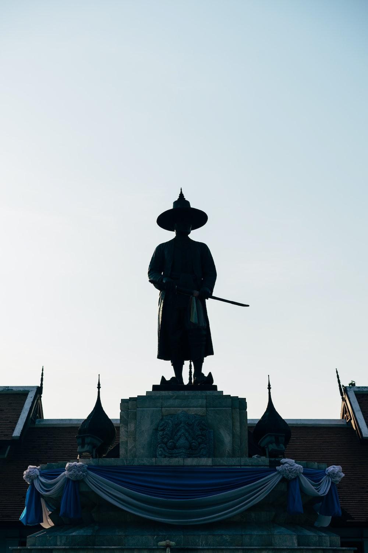 man in black coat statue