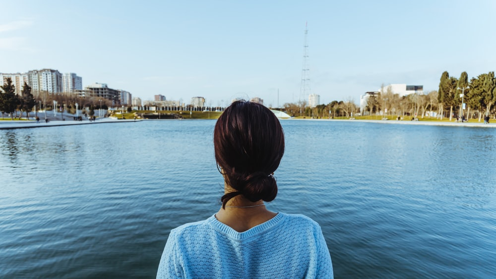 woman in blue knit shirt standing near body of water during daytime