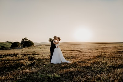 woman in white dress standing on green grass field during daytime bride teams background