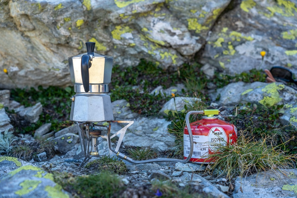 silver and black coffee maker on gray rock