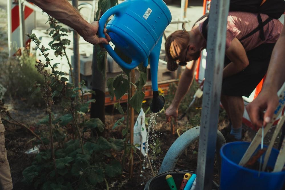boy in blue tank top holding blue plastic bucket