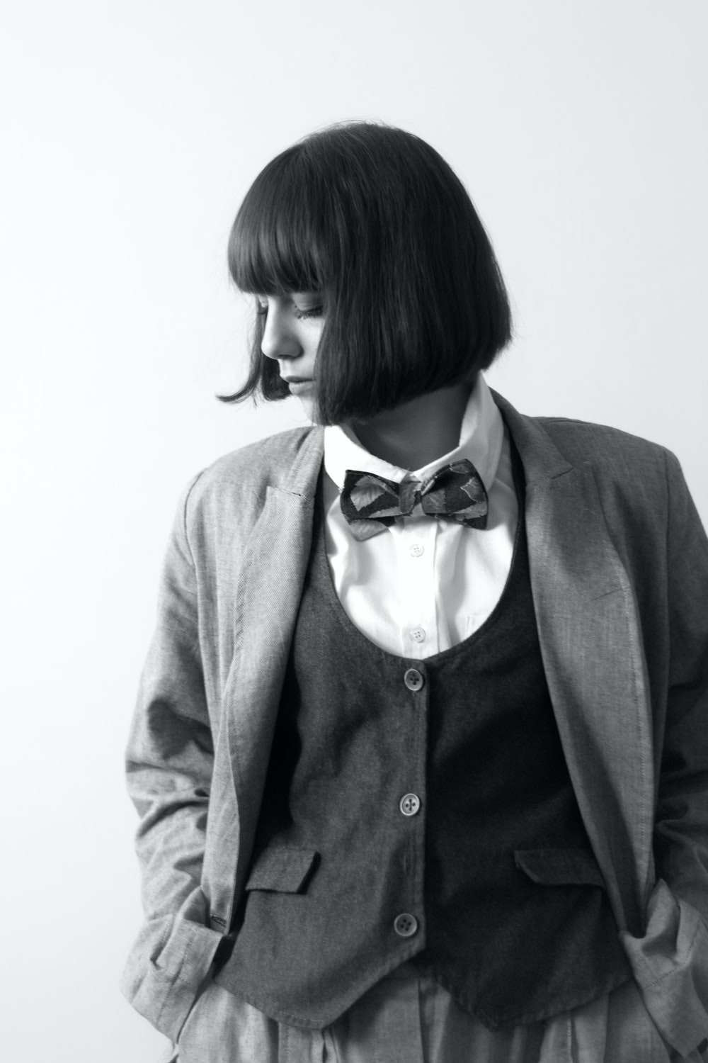woman in gray blazer with black and white polka dots bowtie