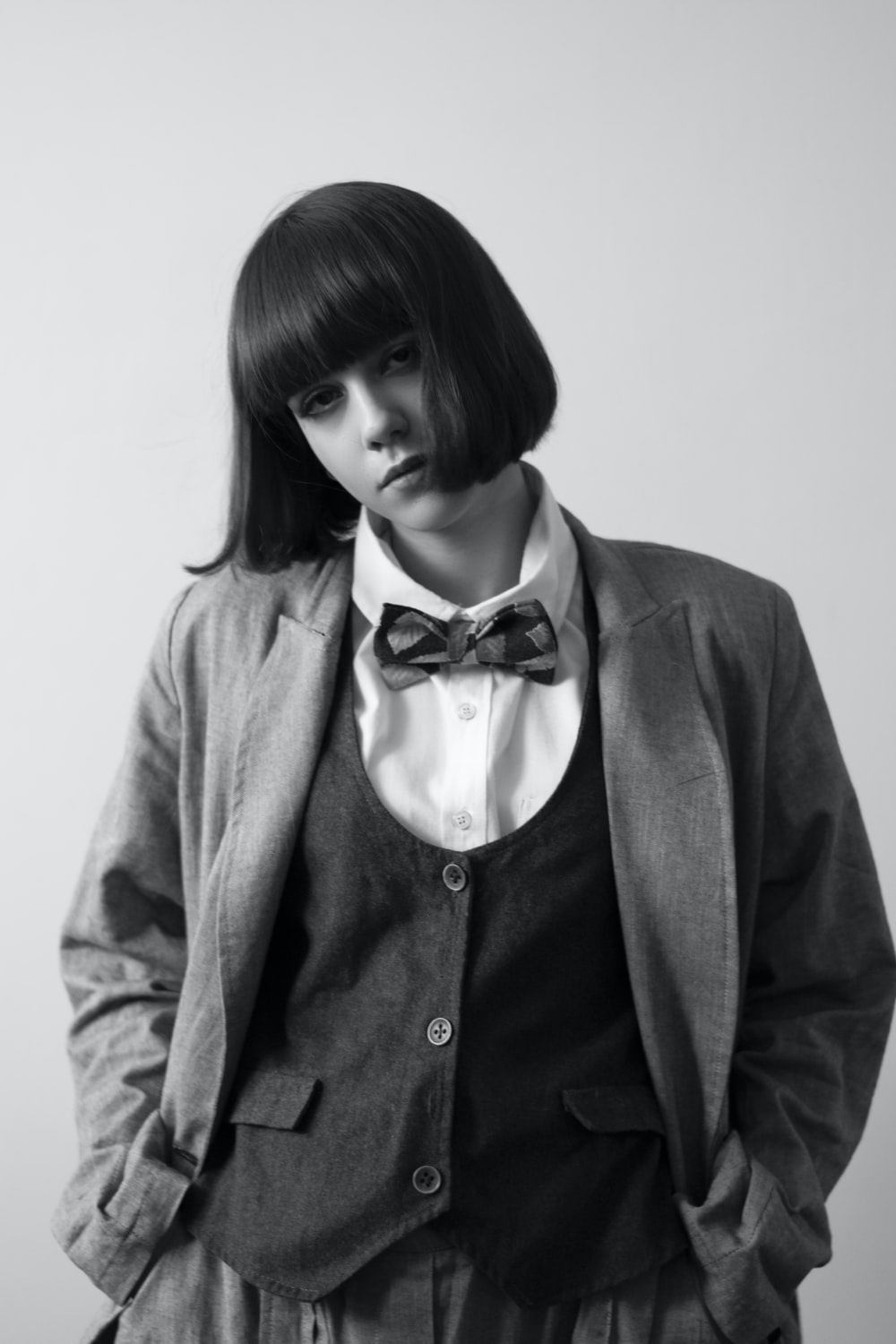 woman in gray blazer with black bow tie