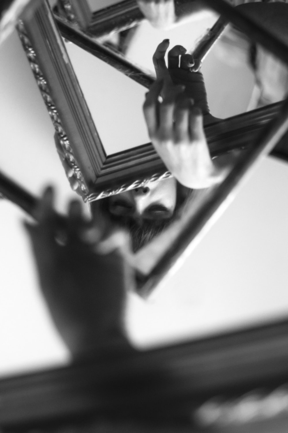 grayscale photo of person holding mirror