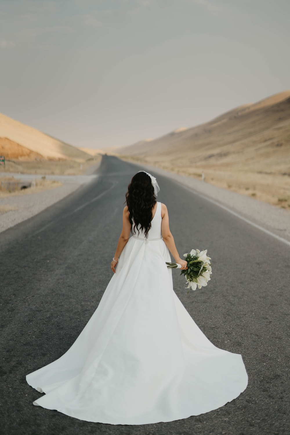 woman in white wedding dress holding bouquet of flowers walking on gray asphalt road during daytime