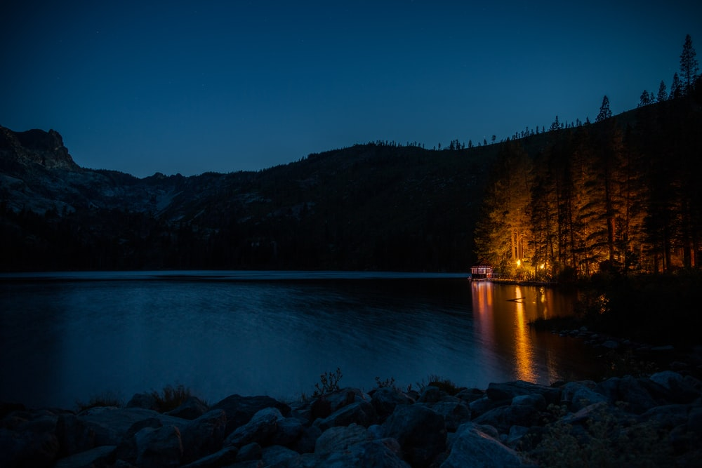 brown wooden dock on blue lake during night time