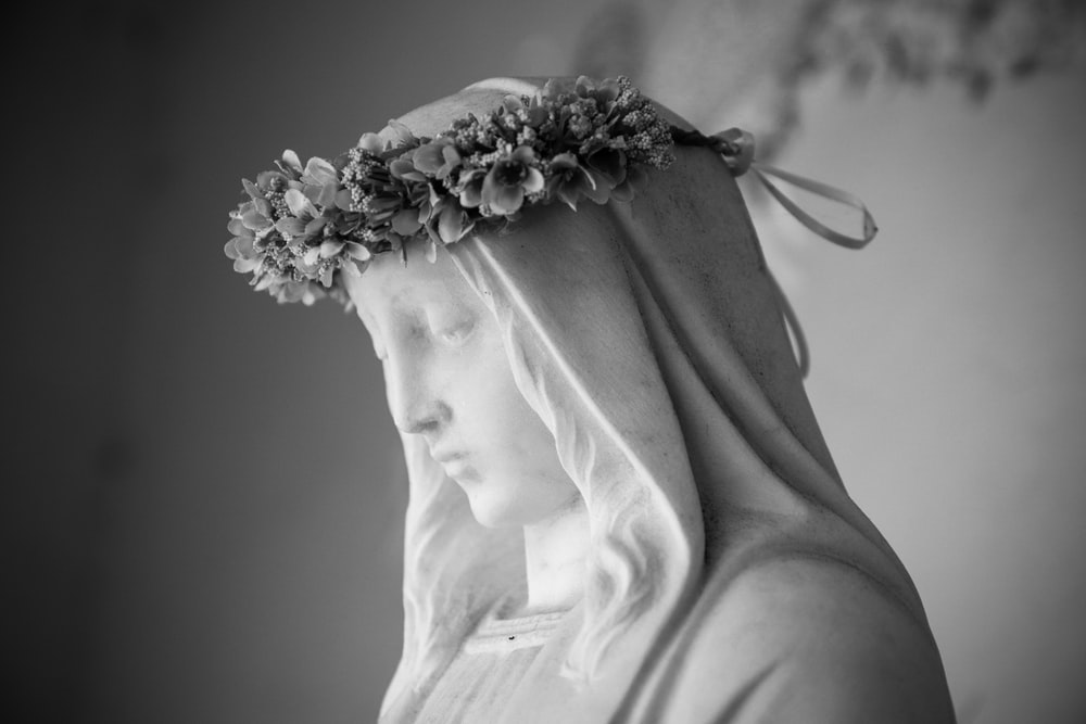 grayscale photo of woman with flower on her head statue