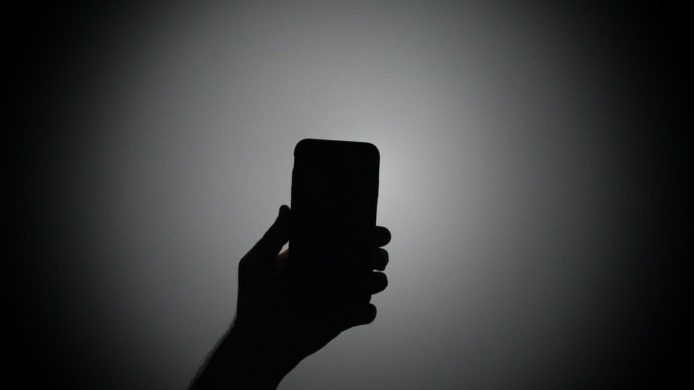 silhouette of person holding smartphone