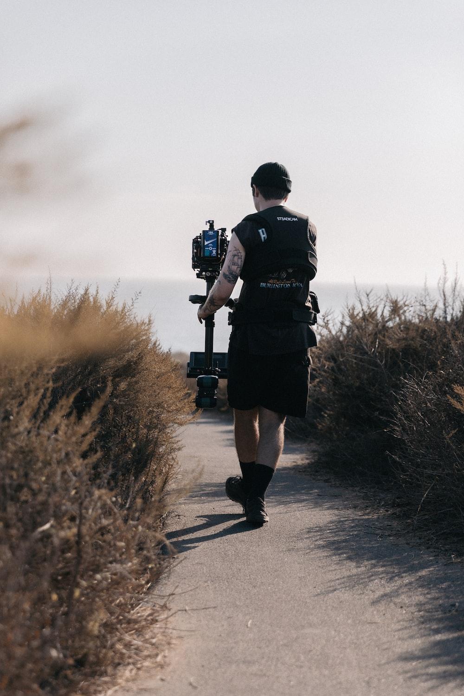 man in black jacket and black shorts carrying black dslr camera