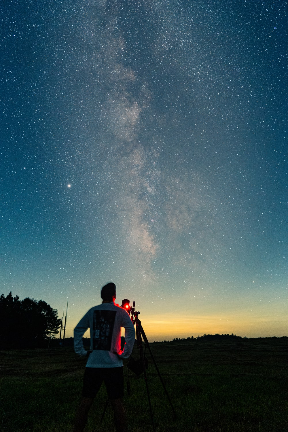 man in red shirt and black backpack standing on grass field under starry night