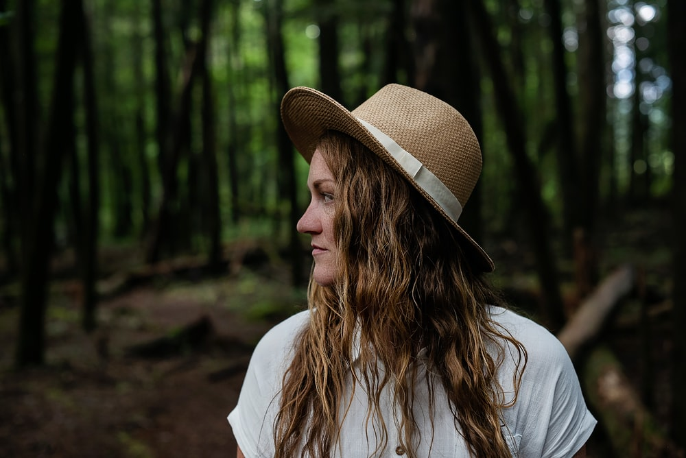 woman in white long sleeve shirt wearing brown fedora hat