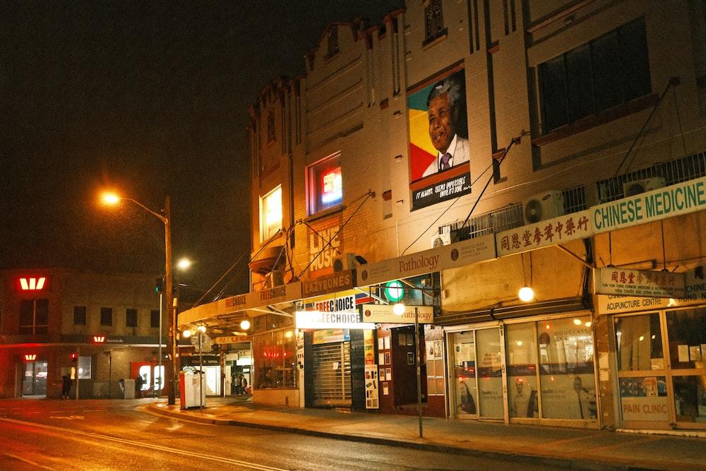 people walking on sidewalk near building during night time