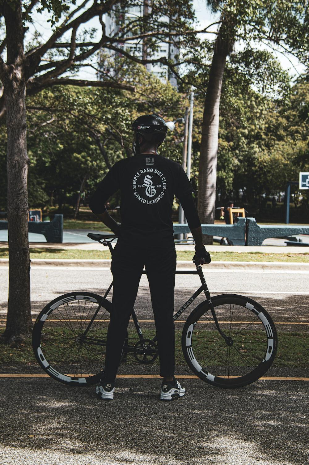 man in black t-shirt and black pants riding bicycle during daytime