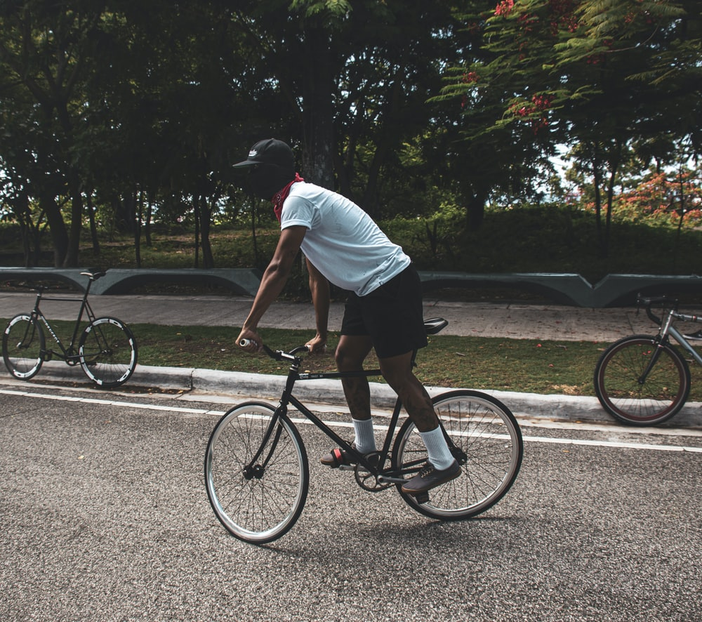 man in white t-shirt riding on black bicycle on road during daytime