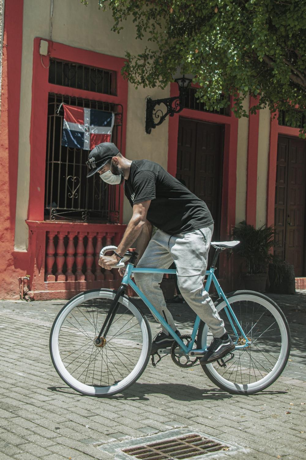 man in black t-shirt riding on teal bicycle during daytime
